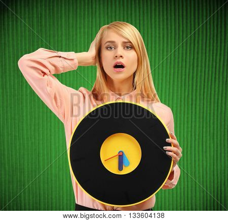 Young attractive woman holds a clock on green background