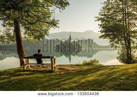 A man relaxing on a bench and looking towards the Church of the Assumption on Bled Lake in the morning