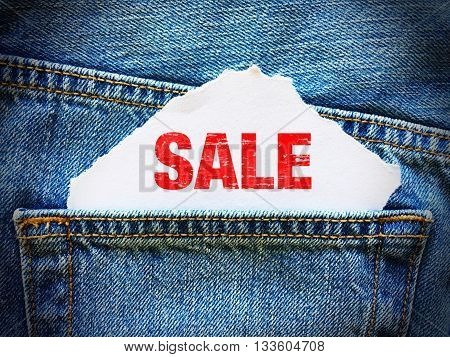 SALE on white paper in the pocket of blue denim jeans
