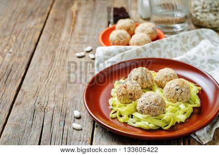 white beans meatballs with zucchini noodles on wooden background