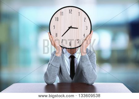 Young man holding clock on blurred background