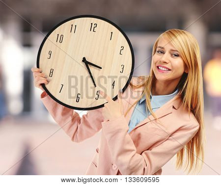 Young attractive woman holds a  clock on blurred background