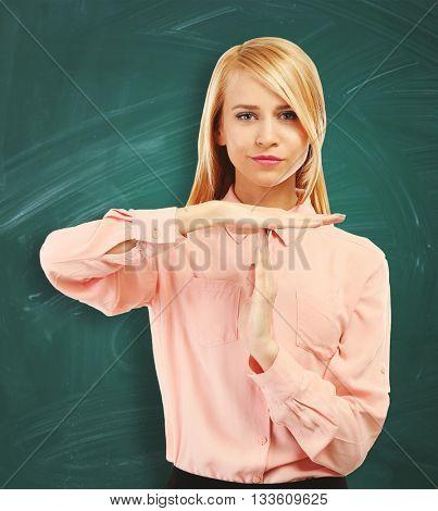 Stressed businesswoman takes a break on blackboard background