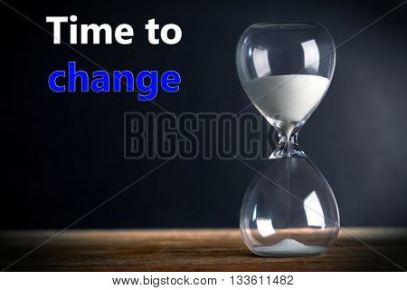 Hourglass on wooden table on grey background