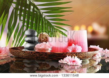 Composition with spa stones, flowers and candles on blurred background