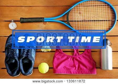Text Sport Time and sport equipment with clothes on wooden background
