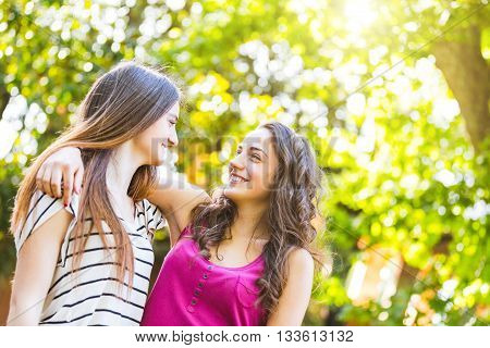 Two Girls Embraced Together At Park