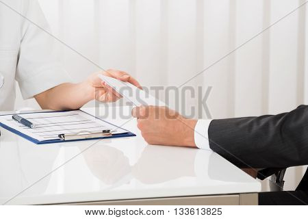 Close-up Of Female Doctor Hand Giving Prescription To Businessman