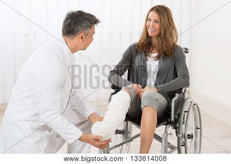 Physiotherapist Examining Leg Of Patient Sitting On Wheelchair