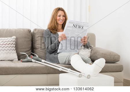 Mature Woman With Fractured Leg Reading Newspaper In House