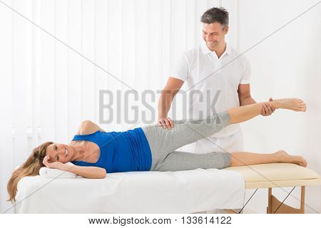 Happy Male Therapist Giving Leg Massage To Mature Woman