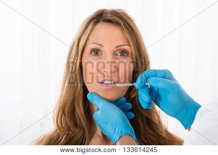 Mature Woman Receiving Cosmetic Injection On Lip In Clinic