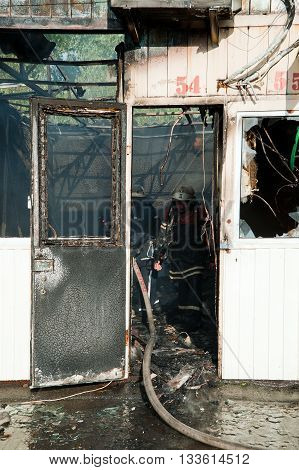 Kiev, Ukraine - June 3, 2016: Firefighters extinguish a large fire at Troyeschina market with water and fire extinguishers
