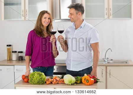 Portrait Of Happy Couple Toasting Red Wine With Vegetables On Countertop In Kitchen