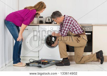 Woman Looking At Repairman Checking Washing Machine In Kitchen