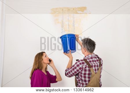 Worker Collecting Water In Bucket From Ceiling While Woman Talking On Mobile Phone