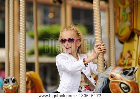 Child On Old French carousel in a holiday park. Elegant Charming cute little girl in fashionable clothes and sunglasses enjoys, sitting on carousel horse.
