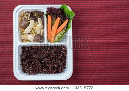 Food series : Stir fry chicken breast with ginger, served with rice berry and fresh vegetable in plastic box, Thai foods