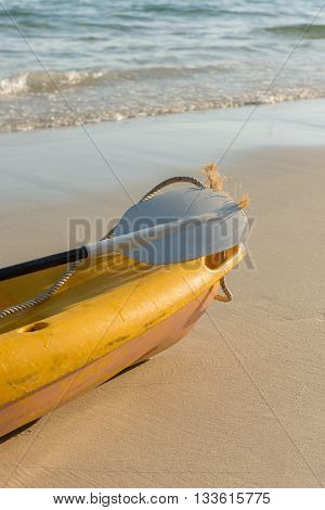 The emty yellow kayak on the beach ready for paddler.