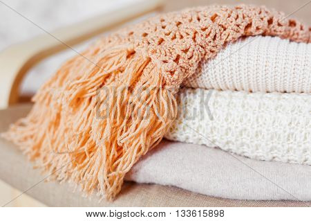 Pile of beige woolen clothes. Warm knitted sweaters and scarfs are folded in one heap.