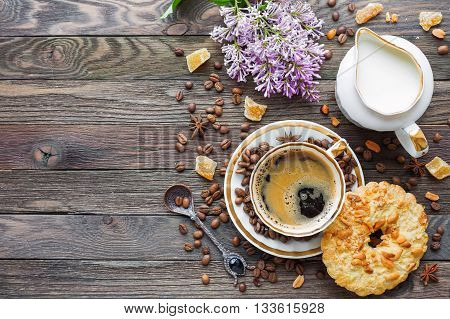 Rustic wooden background with cup of coffee milk peanut tart sugar ginger and lilac flowers. White vintage dinnerware and spoon. Breakfast at summer morning. Top view place for text.