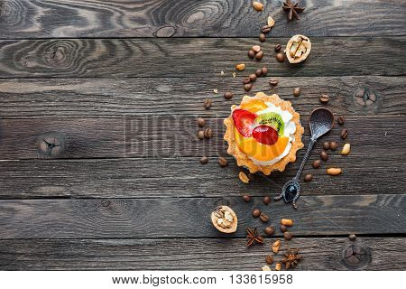 Wooden rustic background with fruit tart and spices - peanuts anise stars coffee beans walnuts. Tasty dessert with strawberry kiwi orange peach and whipped cream. Place for text.