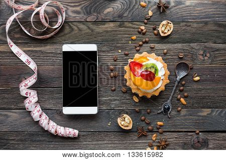 Wooden rustic background with fruit tart and spices - peanuts anise stars coffee beans walnuts. Tasty dessert with strawberry kiwi orange peach and whipped cream. Smartphone and tailor's ruler. Diet concept good for mock up.