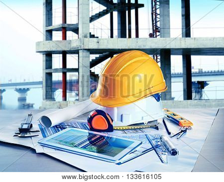 Table with construction drawings and other tools on unfinished building background