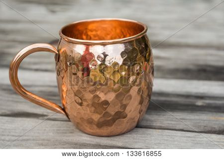 Hammered copper mug sitting on wood table