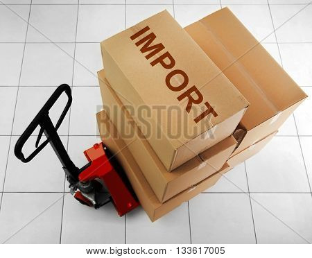 Manual pallet truck with carton boxes and text Import