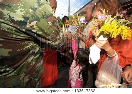 SARABURI ,THAILAND -JULY 7, 2009  : Many Unidentified People Give Flowers to Buddhist Monks for alms in The Tak Bat Dok Mai (give flowers to monk) Ceremony at Phrabuddhabat Woramahavihan Temple on July 7,2009 in Saraburi,Thailand.