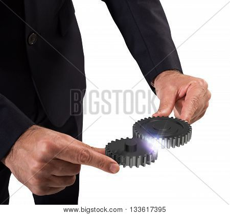 Businessman engages two pieces of mechanism gears