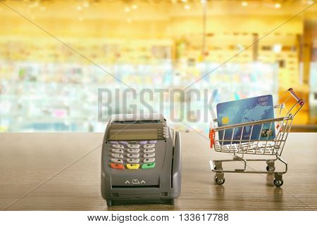 Credit card payment. Payment terminal with supermarket trolley and credit card on wooden table