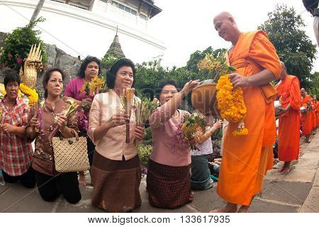 SARABURI,THAILAND -AUGUST 2,2012 : Group of monks receiving flower offering from people in Tak Bat Dok Mai or Flower Offering Ceremony at Phrabuddhabat Woramahavihan Temple , Saraburi Province,Thailand.