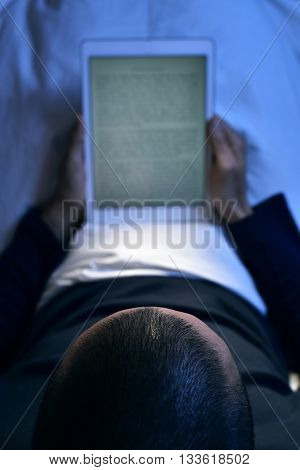 a young caucasian man lying in bed reads an e-book in his tablet computer, at night