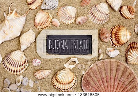 high-angle shot of the sand of a beach full of different seashells and a rustic wooden label-shaped chalkboard with the text buonna state, happy summer in italian, written in it