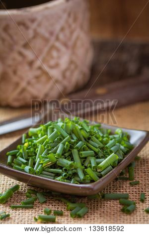 Chopped up chives on a rustic brown dish