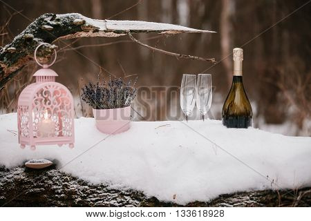 Champagne pouring in two glasses. winter forest.