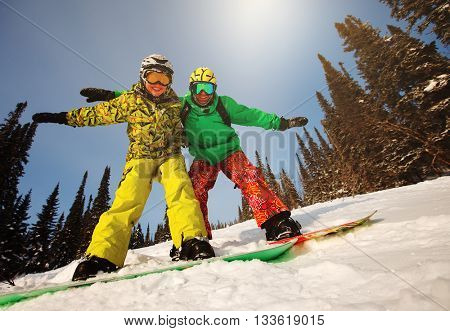 Young couple having fun with snowboards at sunset time.