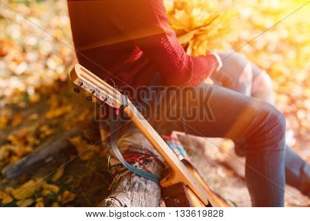 Closeup portrait of a couple sitting with guitar near bonfire in the forest.