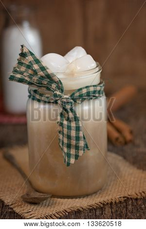 Cold creamy drink in an glass mason jar mug with homespun fabric