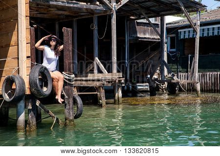 Young beautiful woman with straw hat in sunglasses sitting on a pier