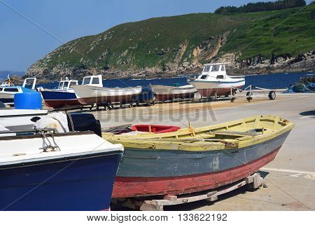 Colorful boats in a sea port with a green landscape as background in Galicia, Spain. Photo taken on: June 6th, 2016