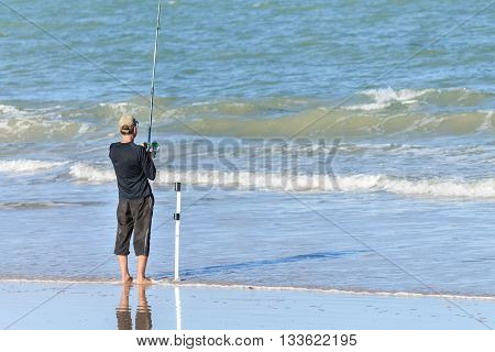Man fishing on the beach on a sunny afternoon