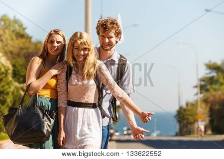 Young people friends hitchhiking on summer vacation. Happy women and man tourists beside road with thumb up gesture having fun.