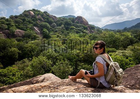 Woman backpacker and photo camera enjoys the beauty of nature hiking in the mountain peak