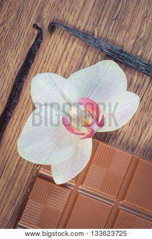 Vintage Photo, Milk Chocolate, Fragrant Vanilla Sticks And Blooming Orchid