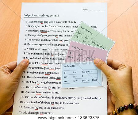 english verb cards in hand over table represent reviewing english grammar