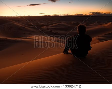 man sitting on a dune in the desert while watching the sunset. Er Chebbi, Maroc, Africa.