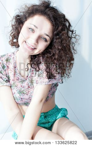 Portrait of a beautiful young girl with brown curly hair. Morning light. Happy and cheerful girl in a t-shirt and short shorts.